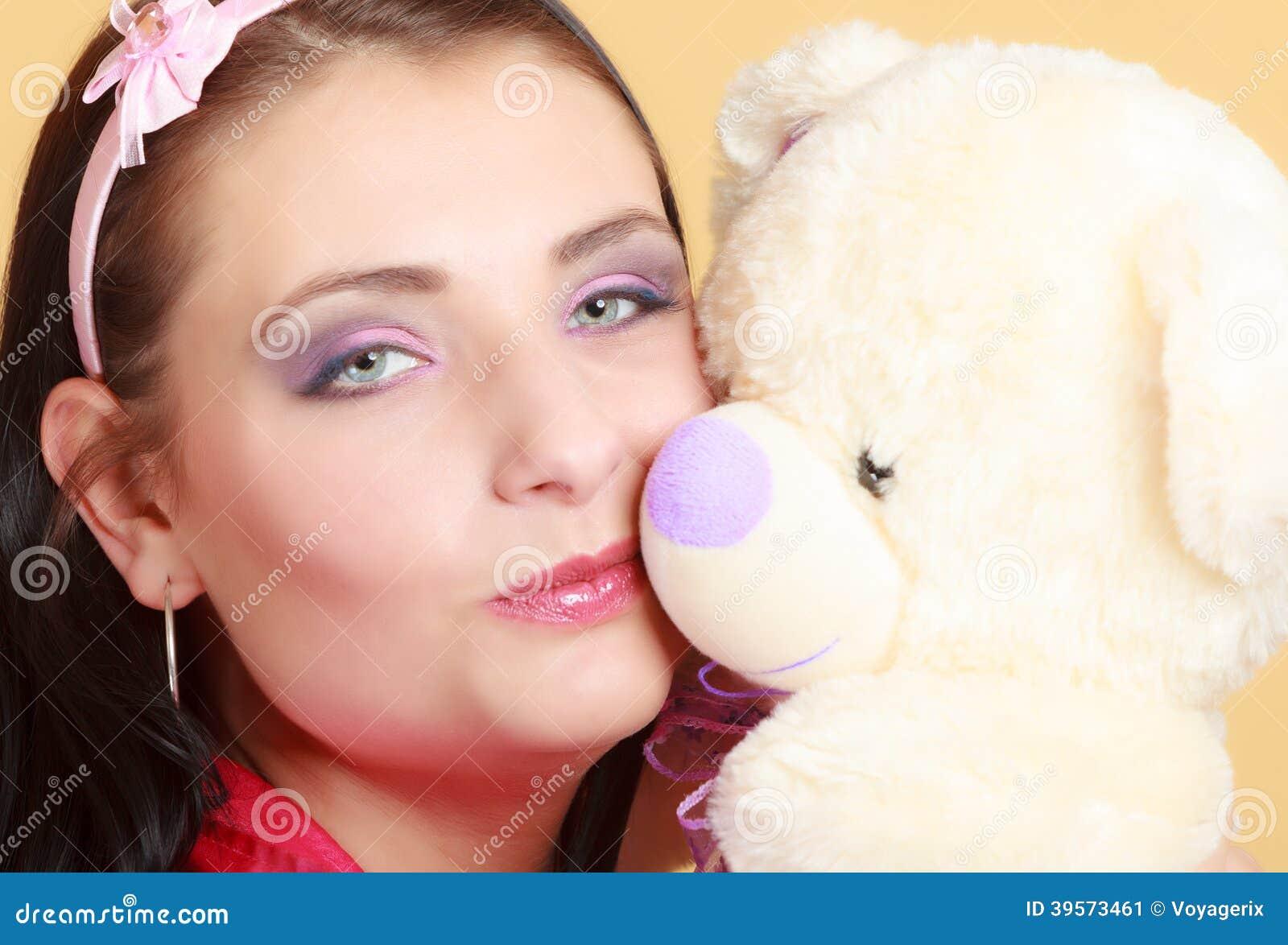 Fille infantile de jeune femme puérile dans le jouet de baiser rose d ours de nounours