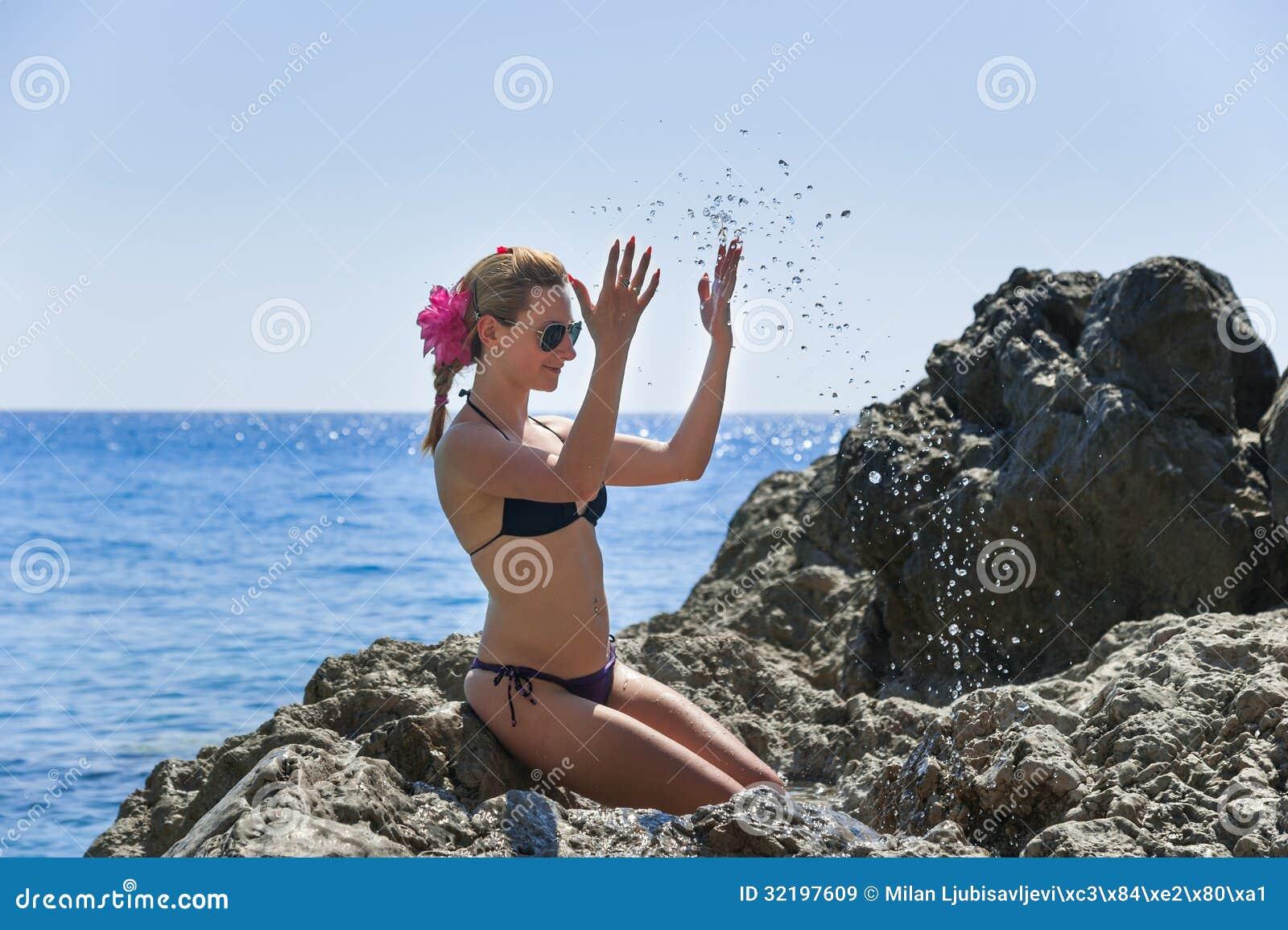 Fille jouant avec de l eau sur la mer