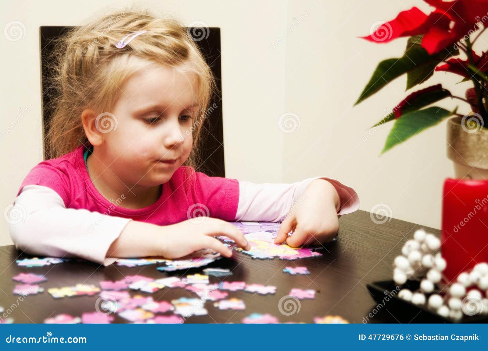 Fille jouant avec le puzzle denteux