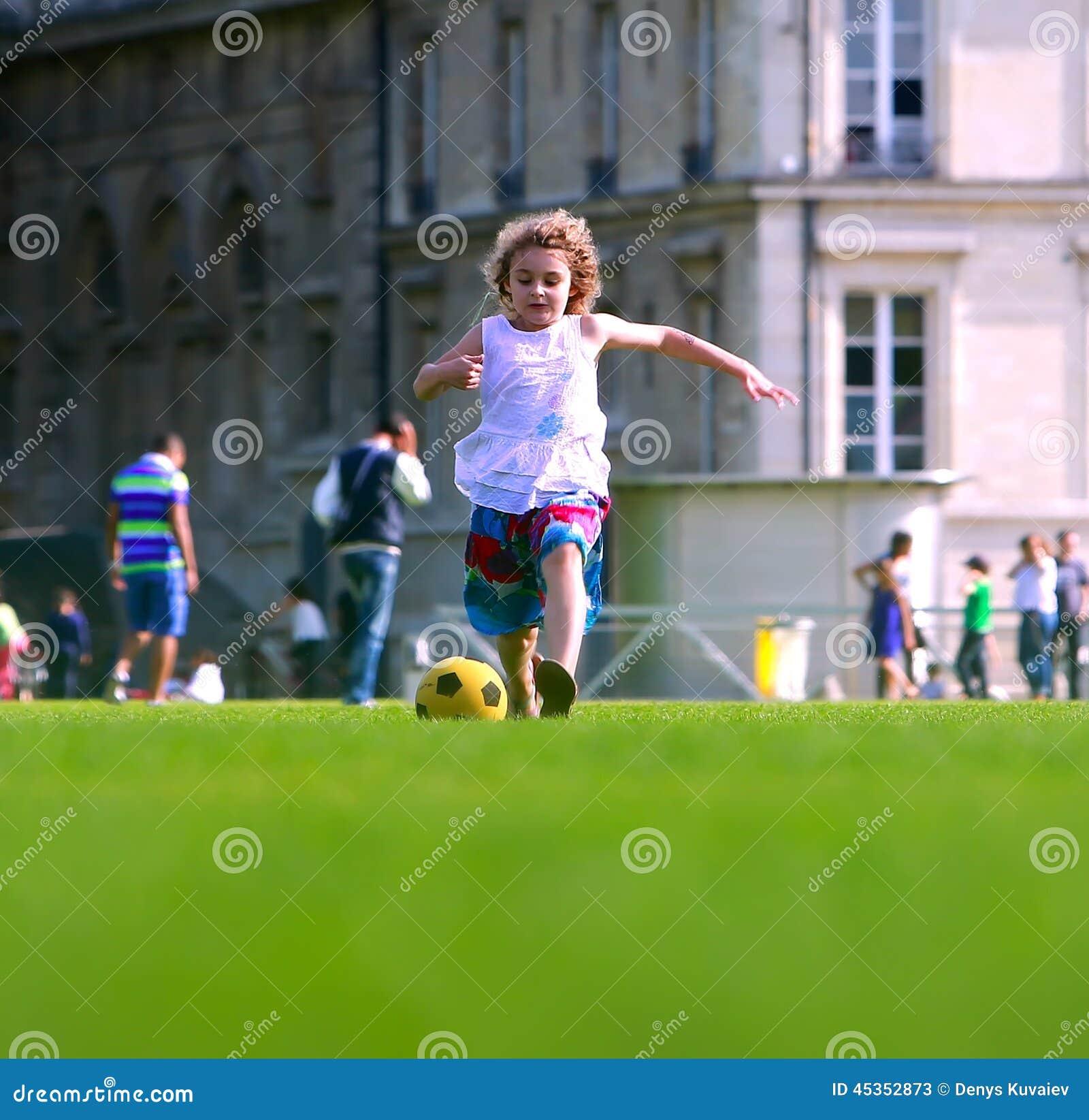 Fille jouant le football dans l avant le bâtiment scolaire