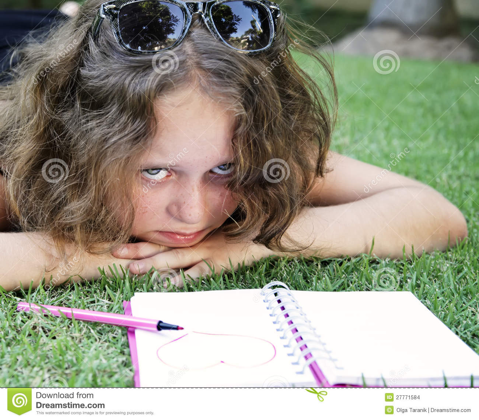 Fille malheureuse se trouvant sur l herbe avec le cahier