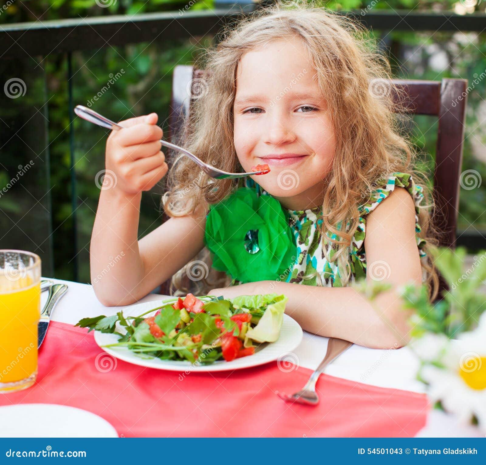 Fille mangeant de la salade à un café