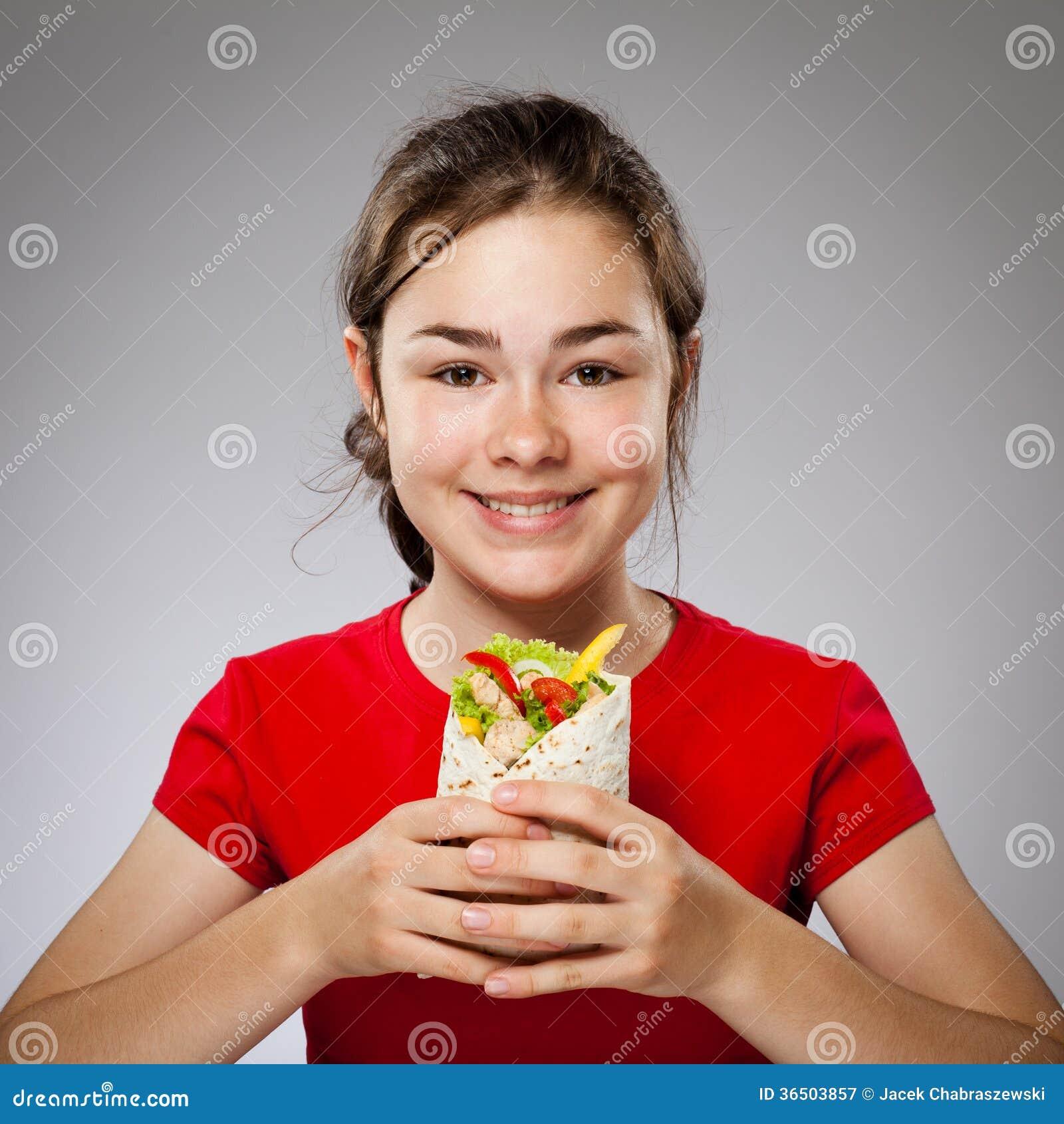 Fille mangeant le grand sandwich - concentrez sur l avant