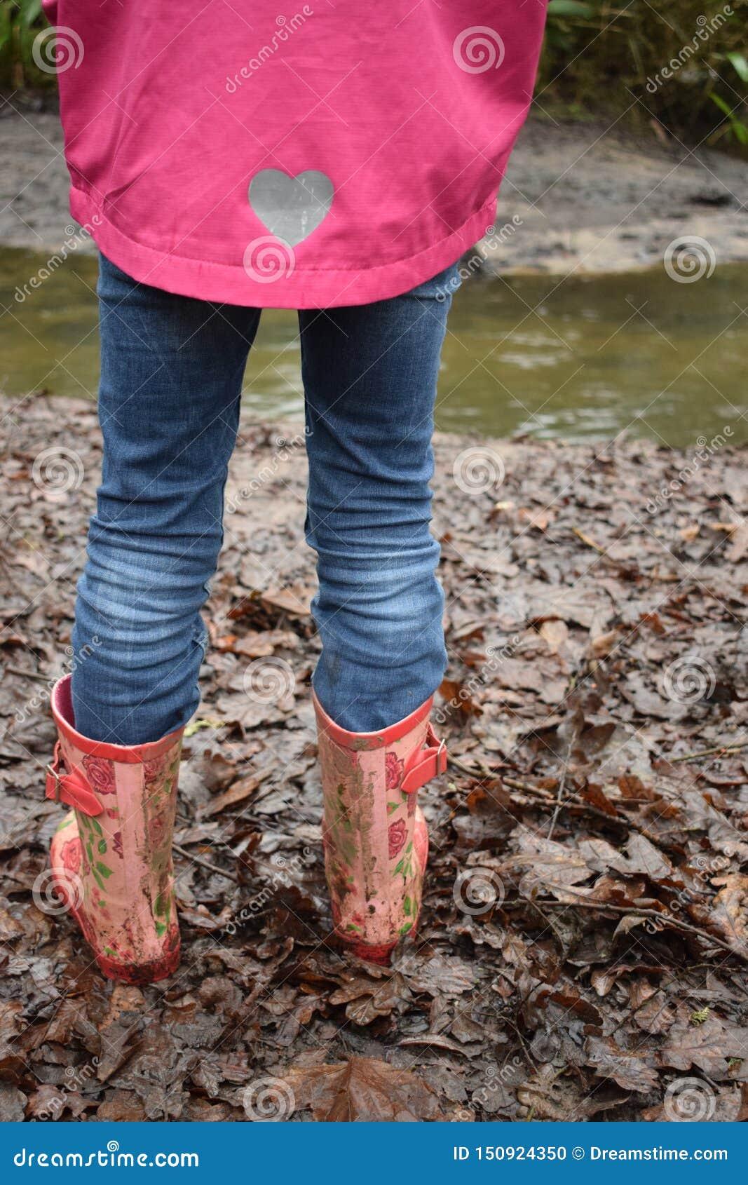 Fille marchant dans les bottes boueuses