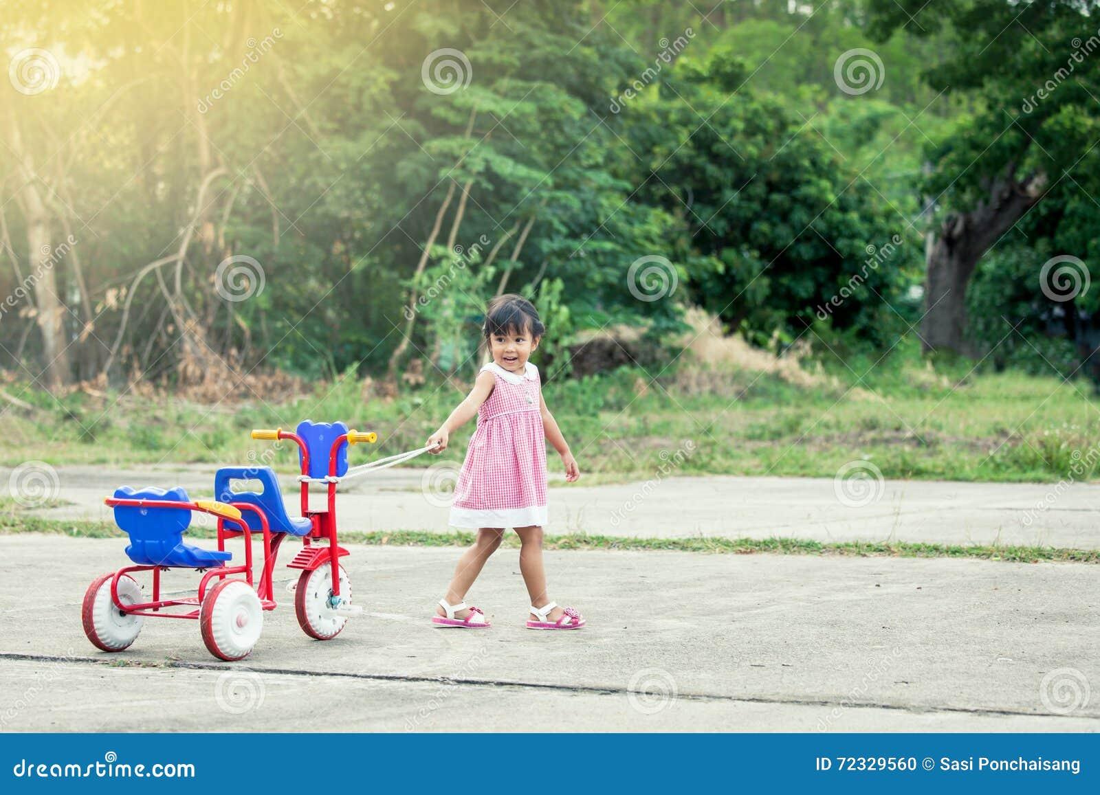 Fille mignonne d enfant petite ayant l amusement pour tirer son tricycle