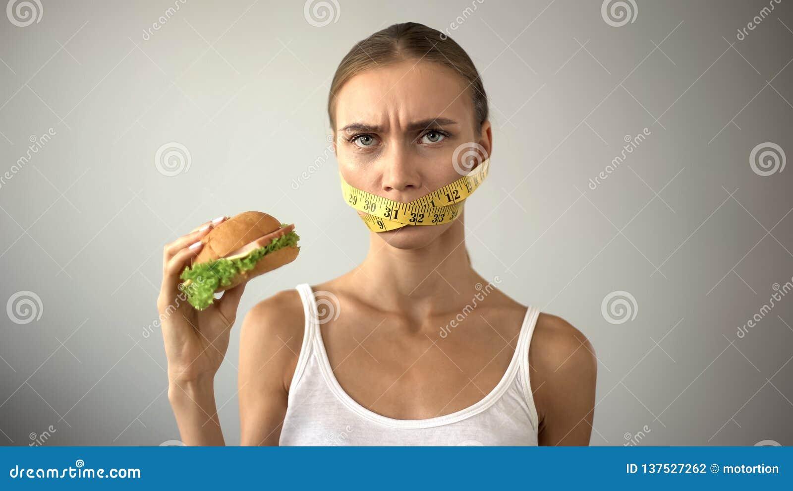 Fille mince avec des combats attachés du ruban adhésif de bouche avec la tentation de manger l hamburger, suivant un régime