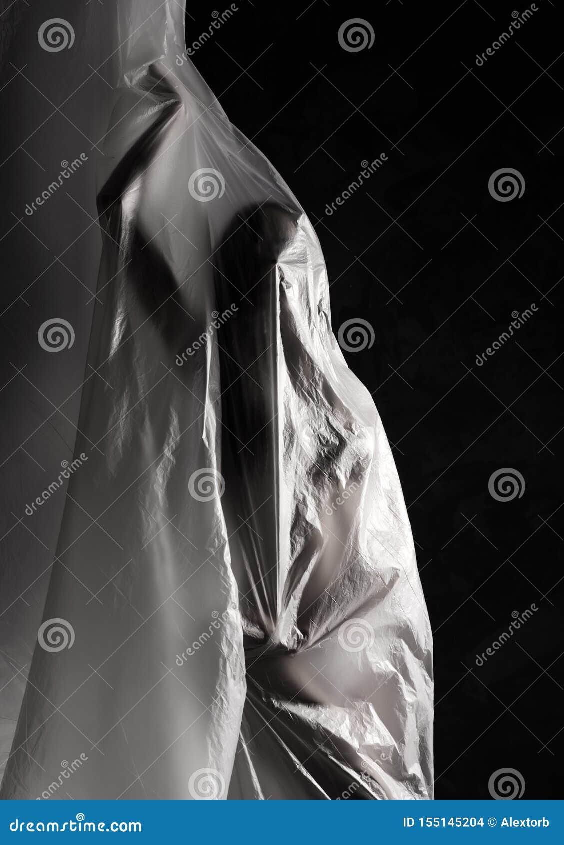 Fille mince habillée seulement dans la pose de sous-vêtements avec émotion, enveloppée le flottement dans le vent et en adaptant