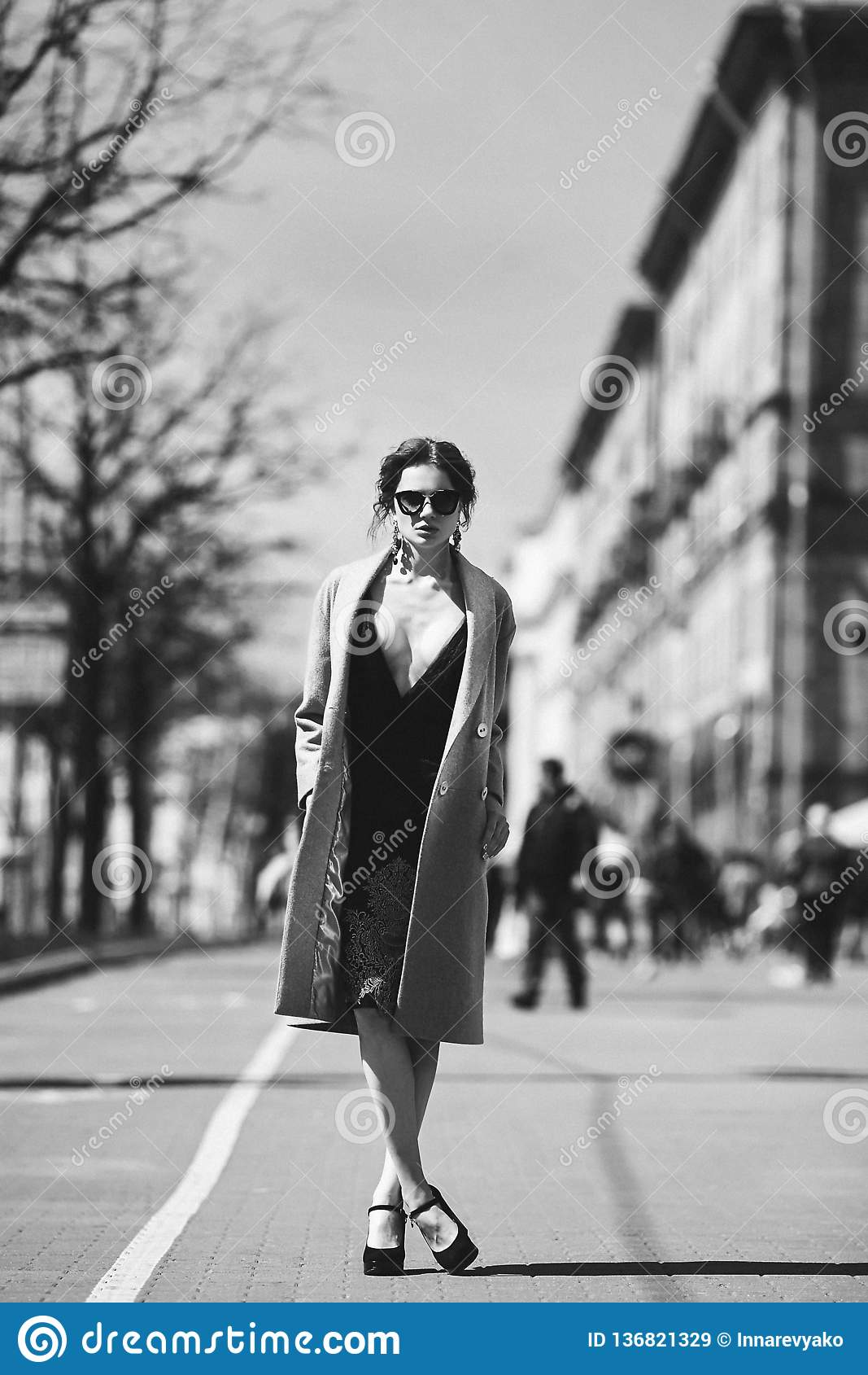 Fille modèle de belle et sexy brune de photo sans couleur - dans la robe élégante noire, dans un manteau à la mode et dedans à la