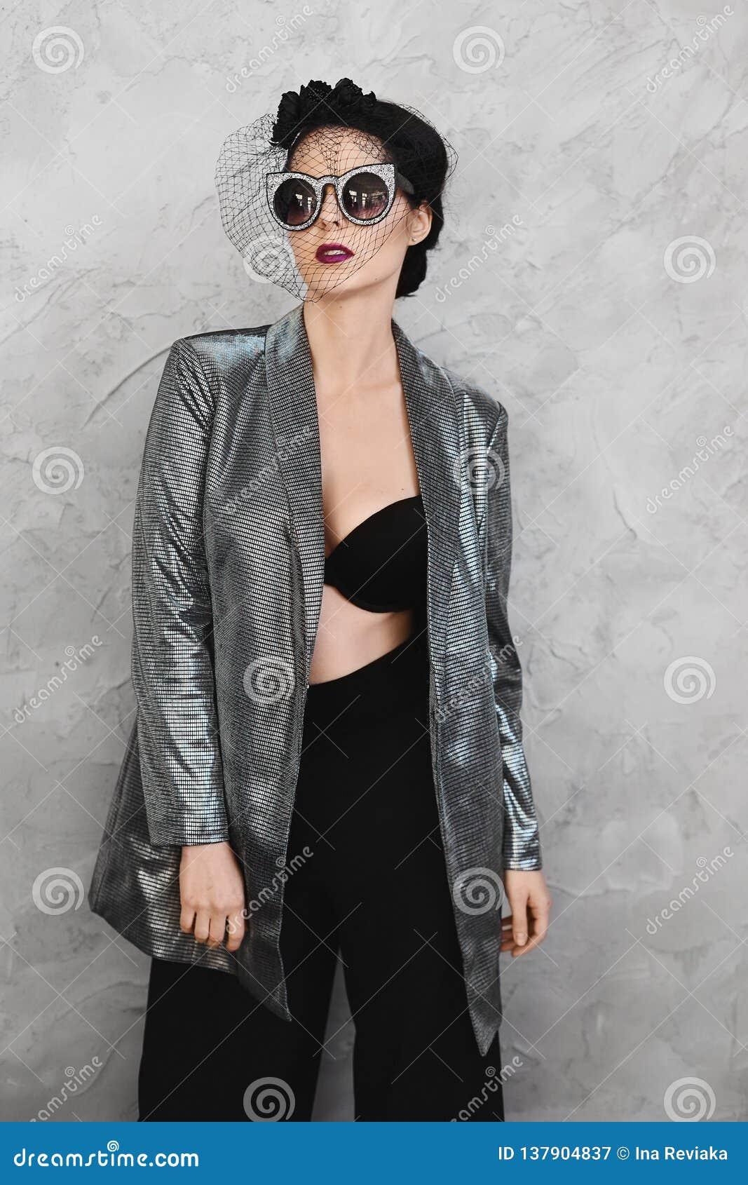 Fille modèle de brune à moitié nue à la mode avec le maquillage lumineux et avec le chapeau élégant dans une veste argentée débou