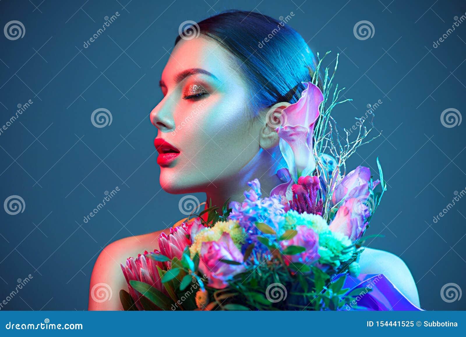 Fille modèle de brune sexy avec le bouquet de belles fleurs Jeune femme de beauté avec le groupe de fleurs dans les lampes au néo