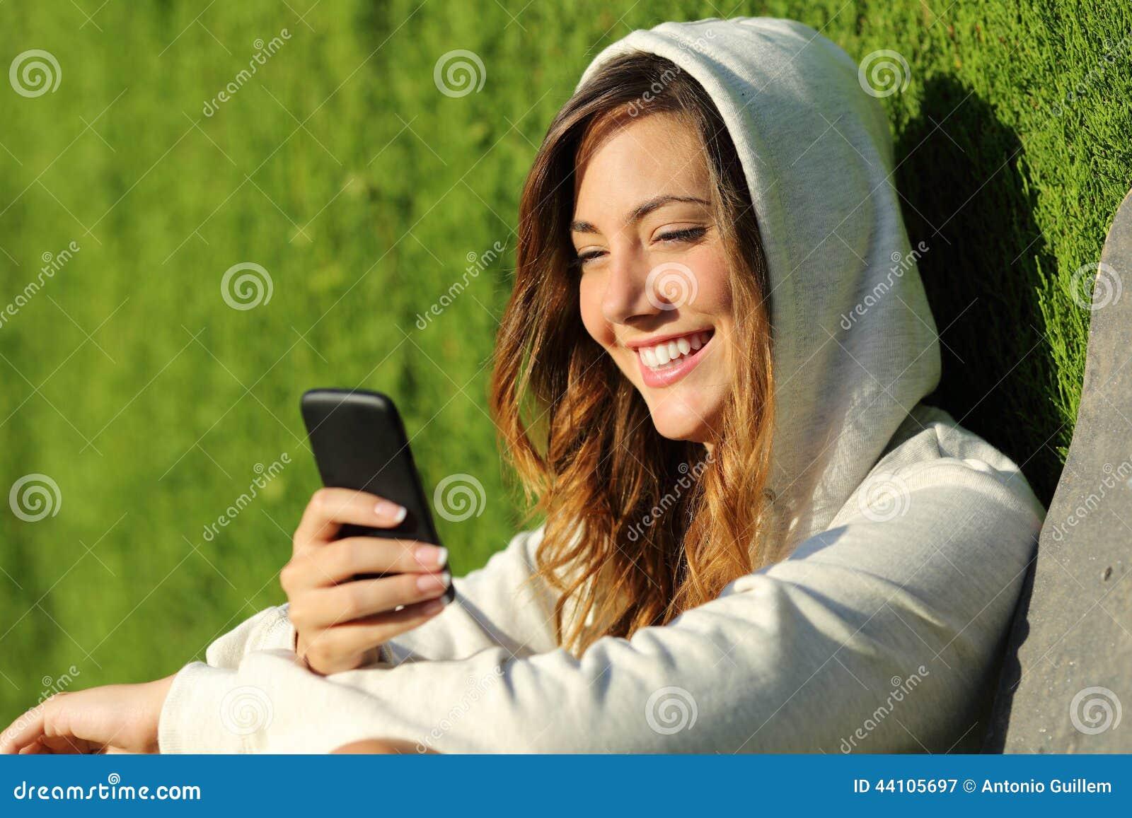 Fille moderne d adolescent à l aide d un téléphone intelligent dans un parc
