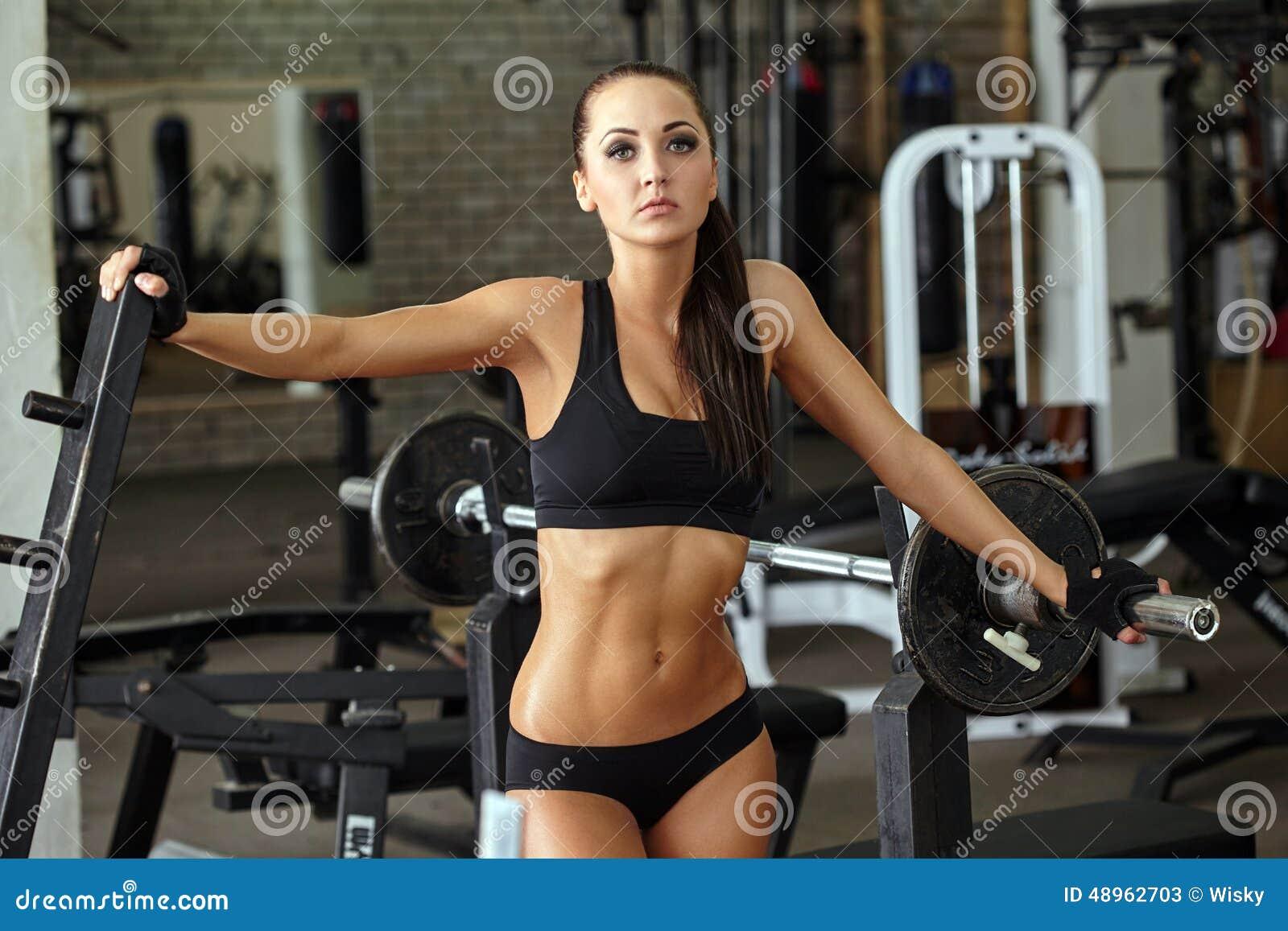 fille musculaire bien faite posant dans le gymnase