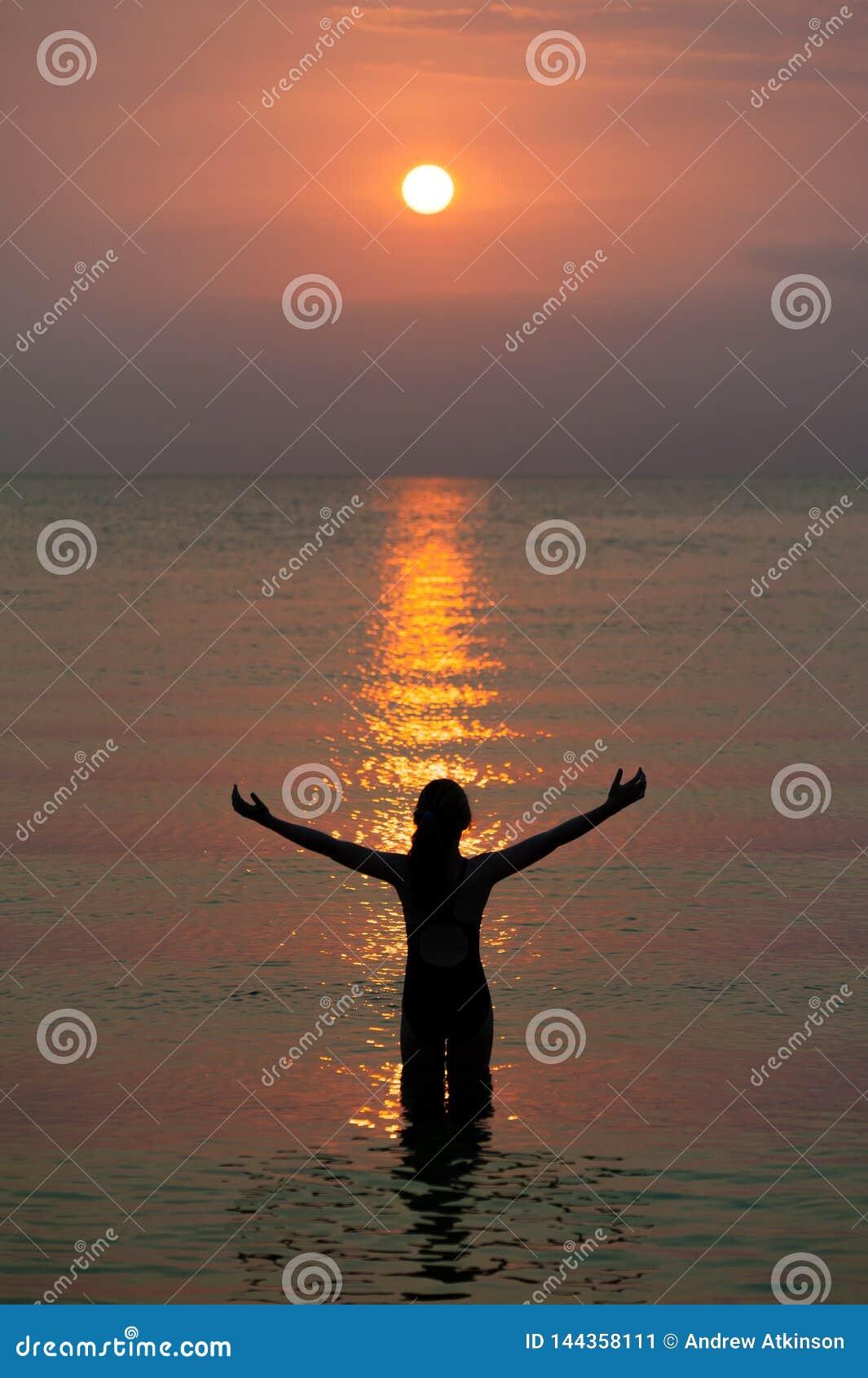 Fille observant le beau modèle reflété du soleil comme un escalier sur le feu