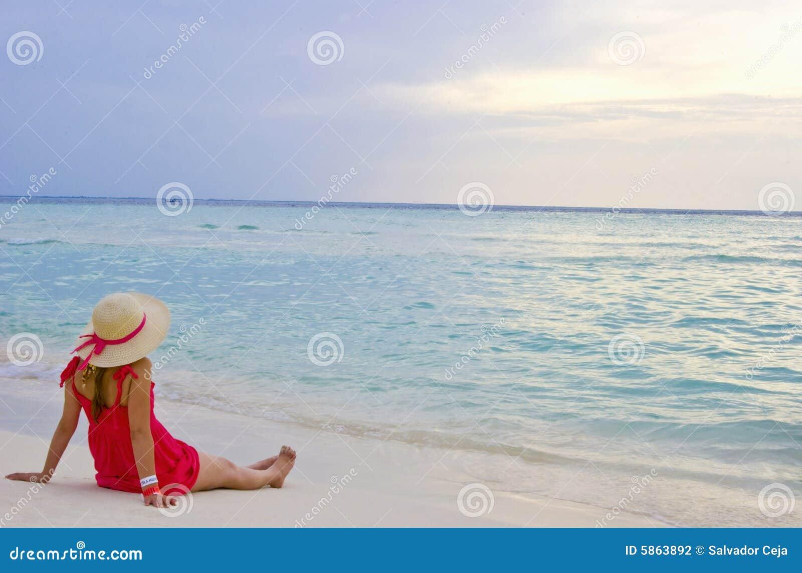 Fille observant le coucher du soleil sur la plage