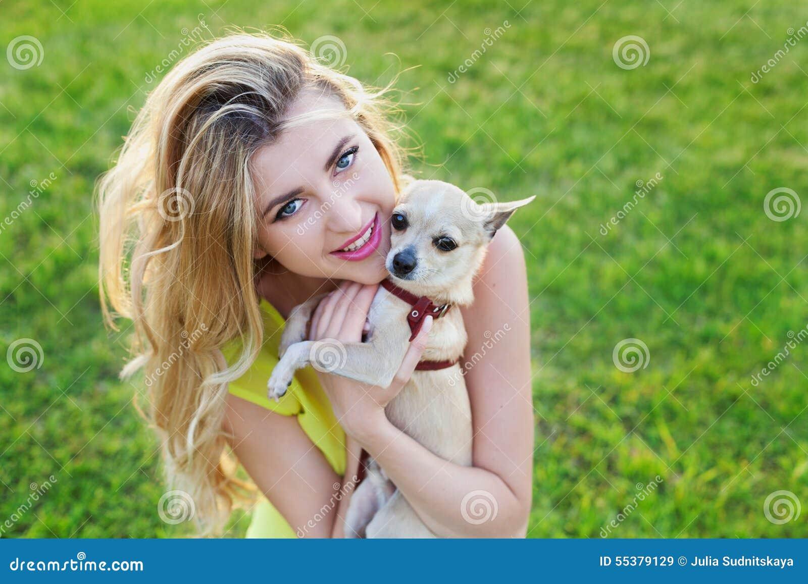 Fille ou femme de sourire heureuse de charme tenant le chiot mignon de chiwawa sur la pelouse verte sur le coucher du soleil