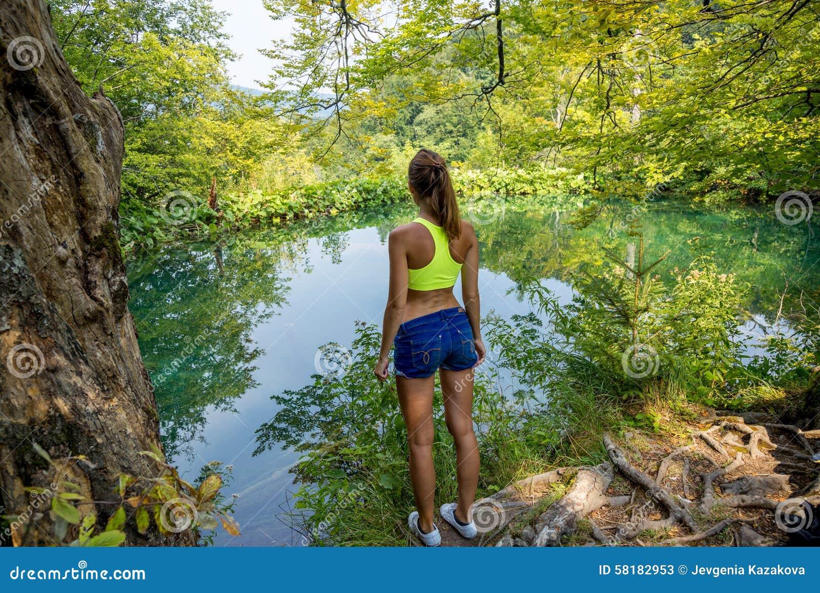 Fille par le lac de forêt