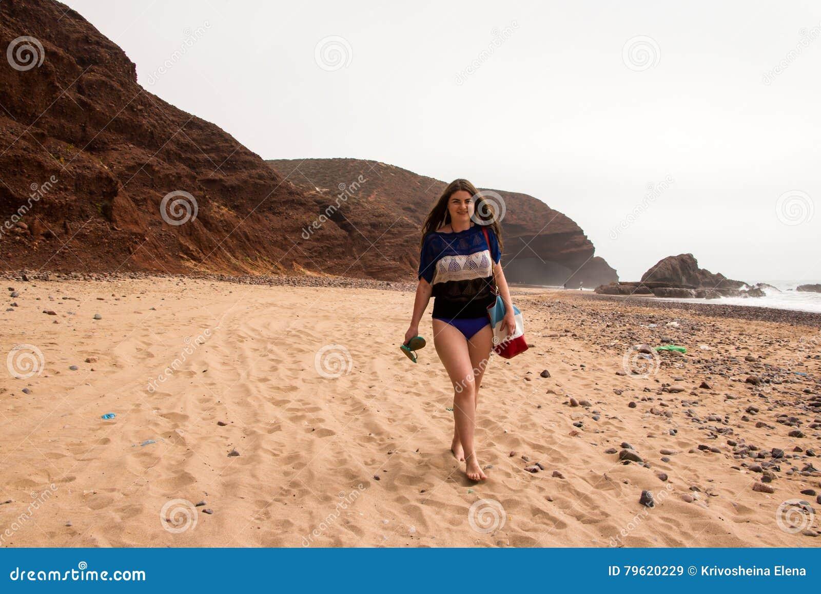 Fille, plage et mer dans le jour nuageux