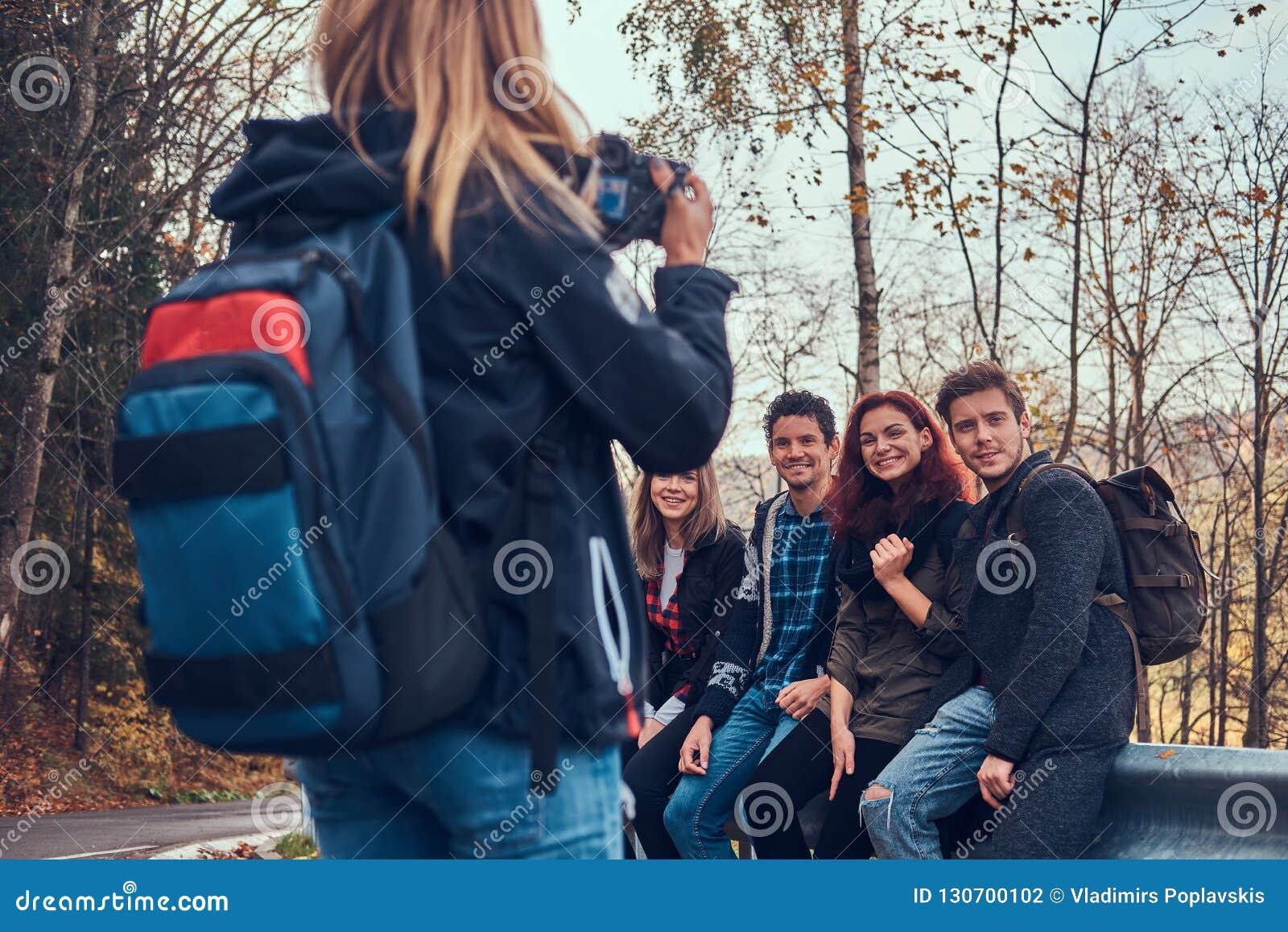 Fille prenant une photo de ses amis Groupe de jeunes amis s asseyant sur la rambarde près de la route