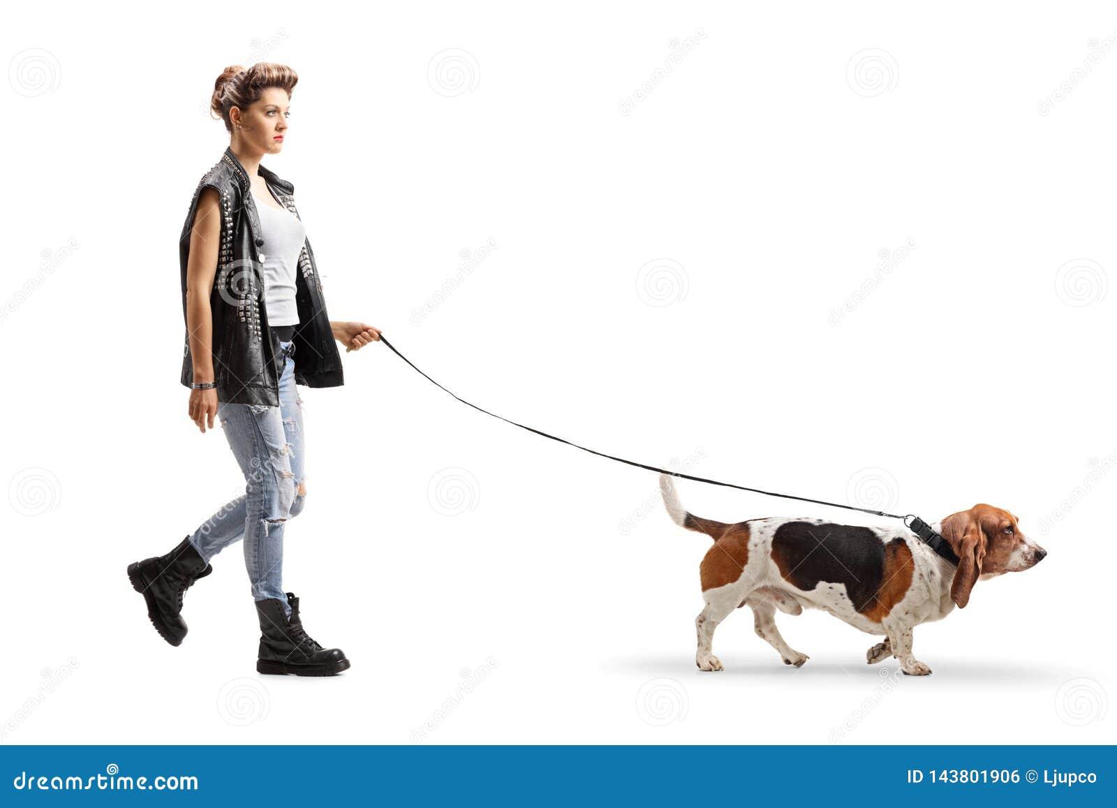 Fille punk marchant avec un chien de chasse de basset sur une laisse