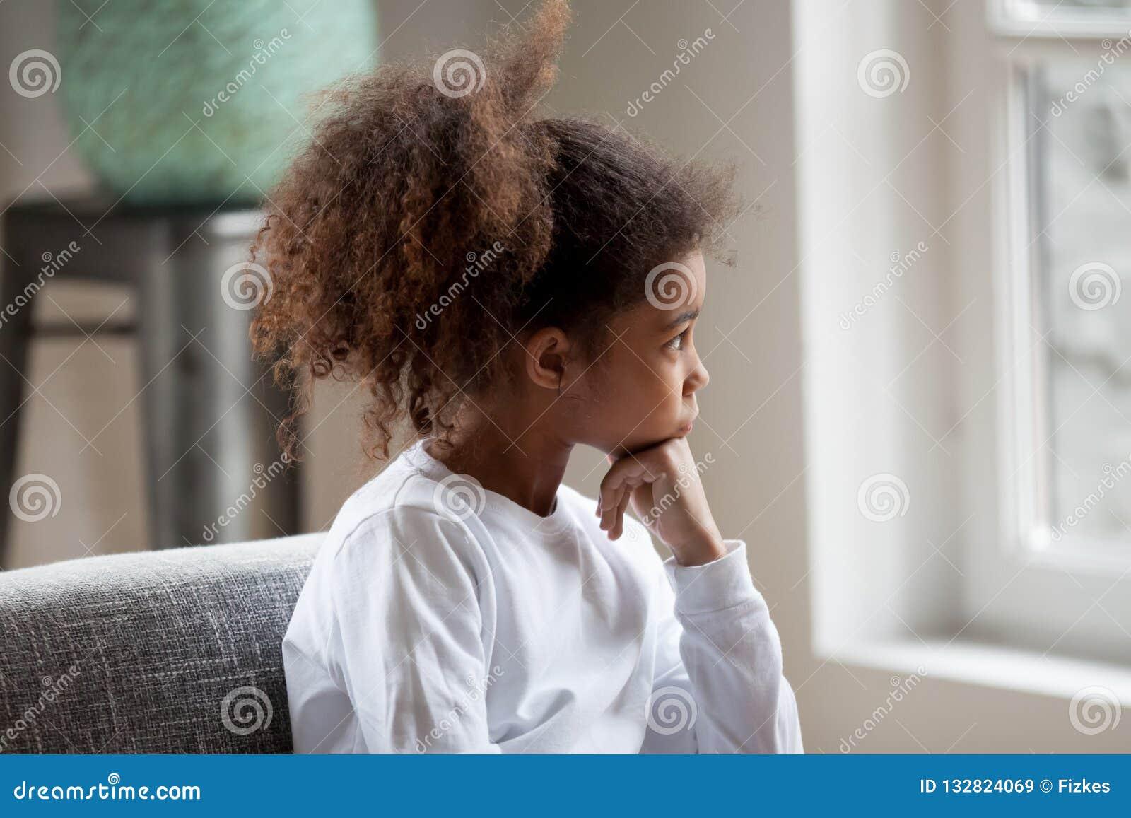 Fille réfléchie d élève du cours préparatoire d Afro-américain regardant dans la fenêtre