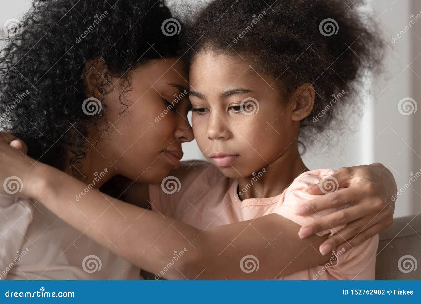 Fille réfléchie d enfant d afro-américain embrassant la liaison de maman caressant