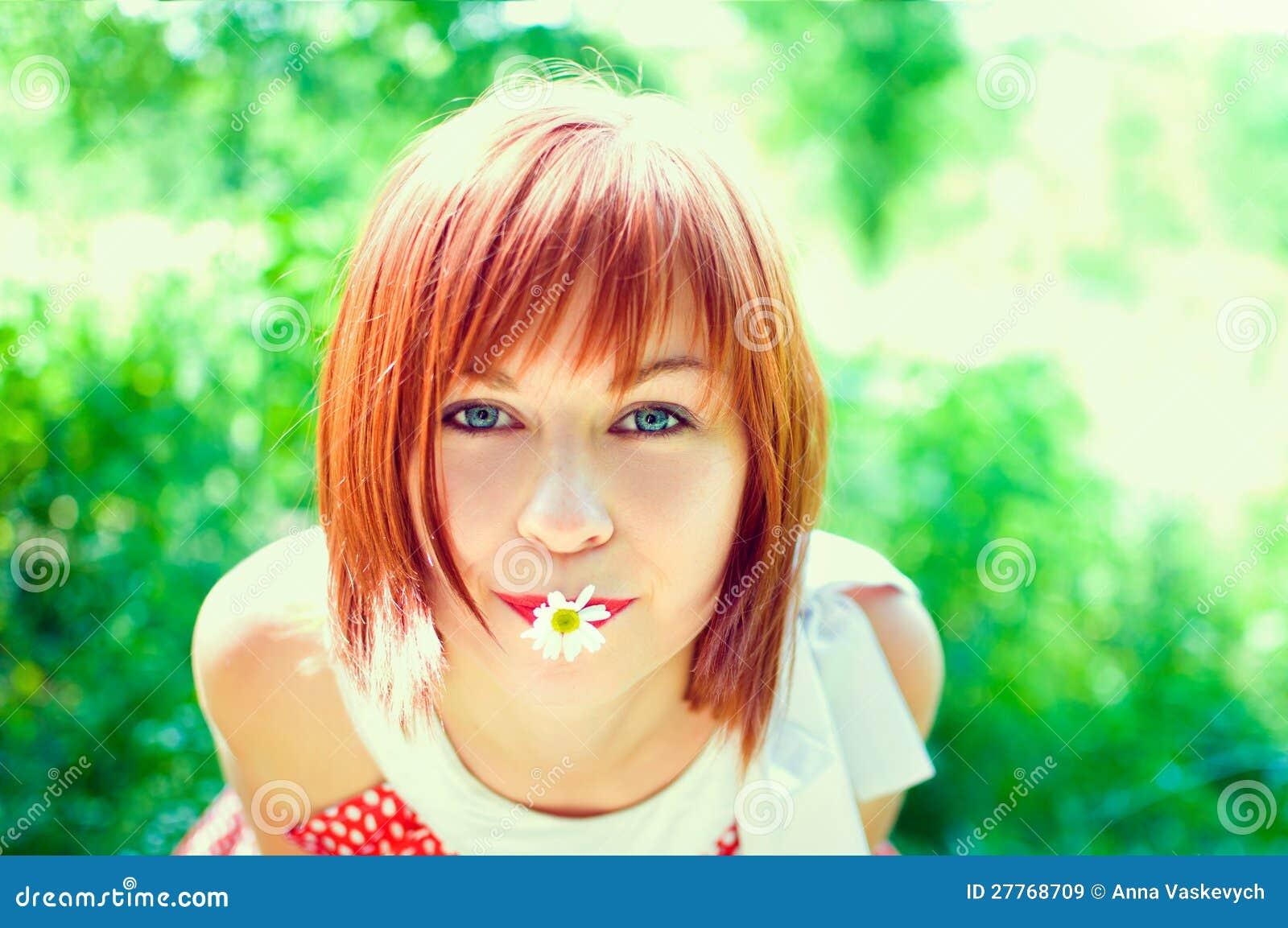 Fille Red-haired avec une fleur dans sa bouche
