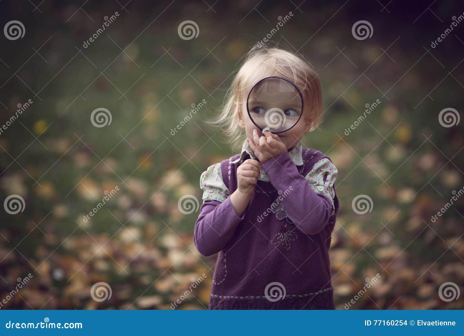 Fille regardant par la loupe dans l automne