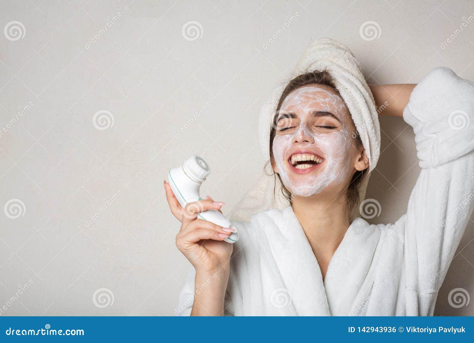 Fille riante de brune posant avec hydrater le décapant crème de masque et de visage L espace vide