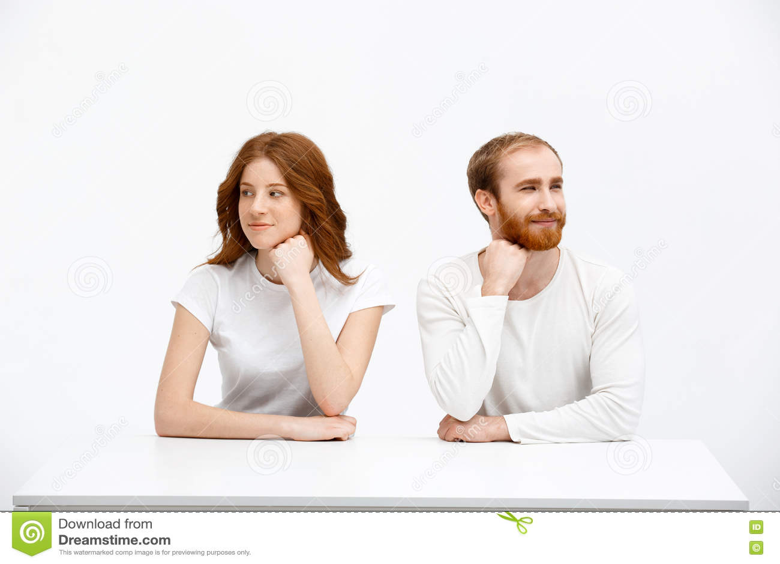 Fille rousse et garçon de tenderless sasseyant au bureau blanc