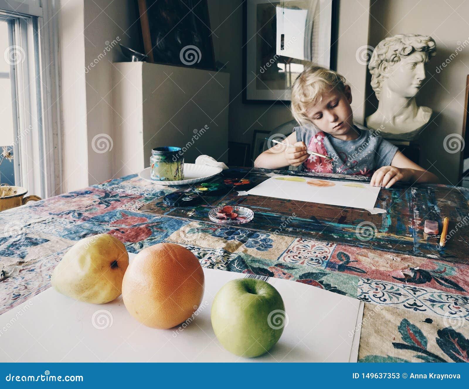 Fille s asseyant dans le studio à la maison d art concentré sur les fruits de peinture avec des brosses et des peintures d aquare