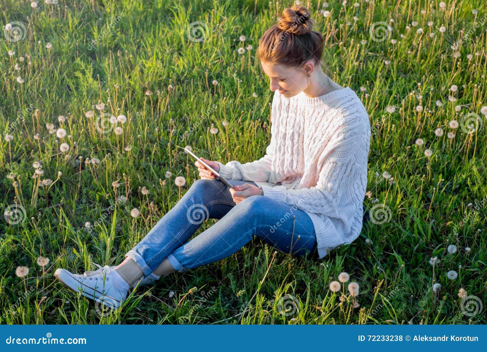 Fille s asseyant sur l herbe et regardant la tablette