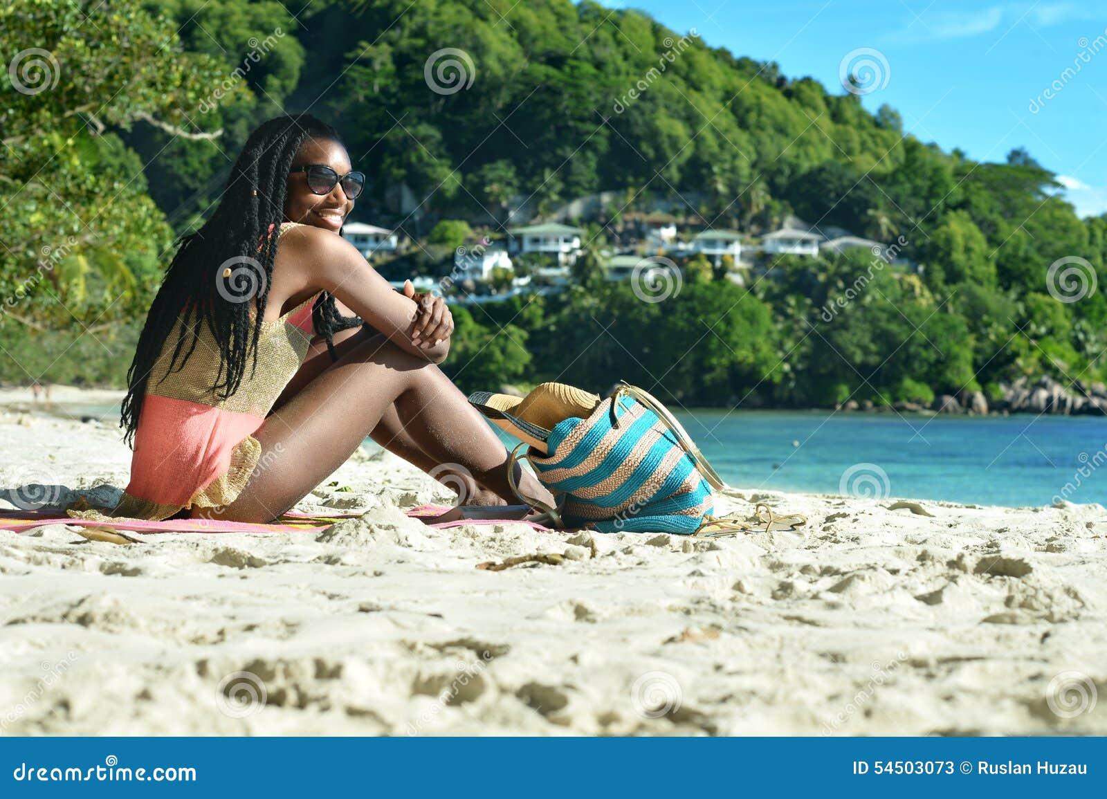 Fille s asseyant sur la plage