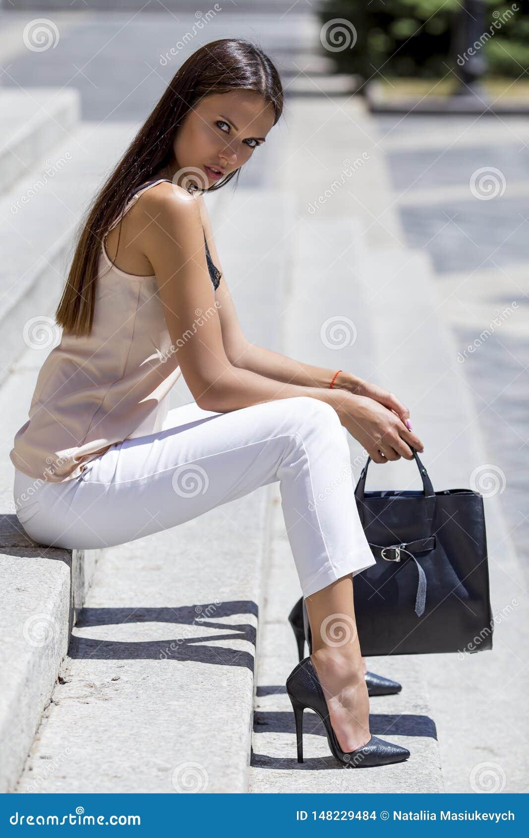 Fille s asseyant sur les escaliers dans des chaussures chics avec un sac noir élégant