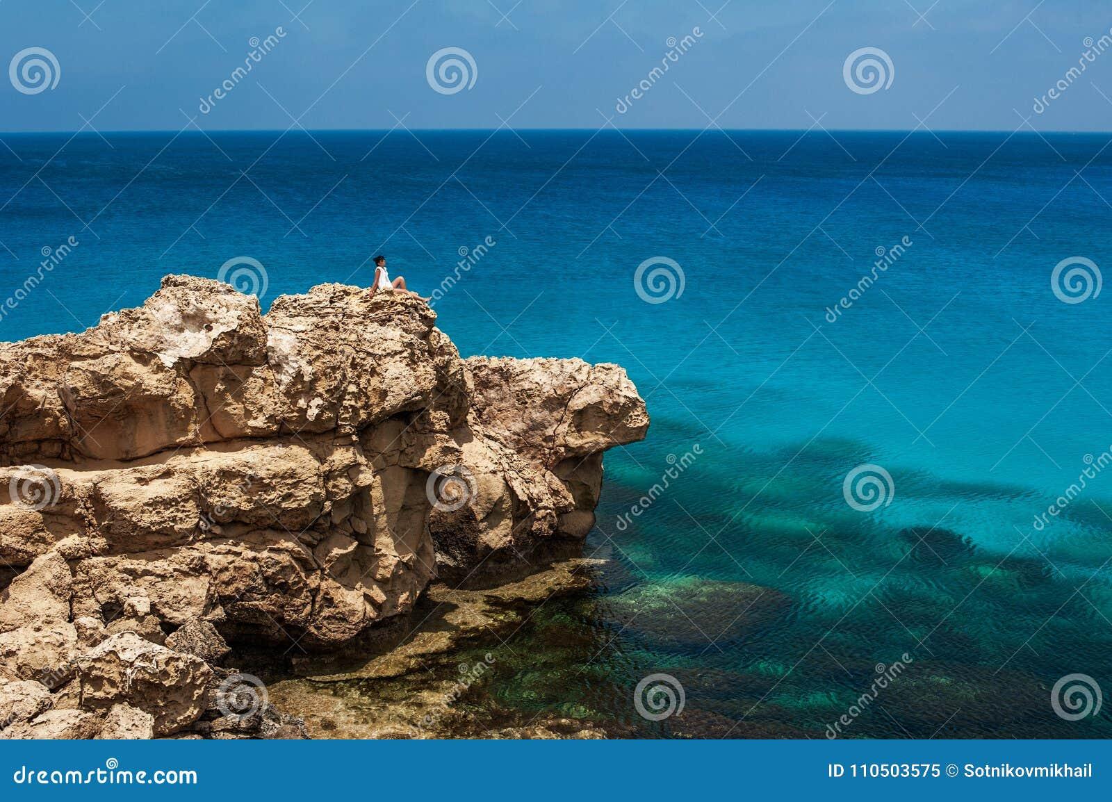 Fille s asseyant sur une roche par la mer