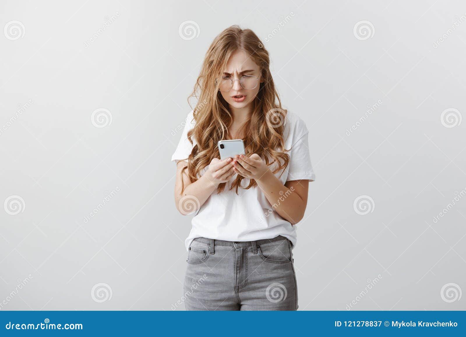 Fille se sentant maladroite envoyant le message au faux numéro Portrait de jeune femme préoccupée attirante en verres, jurant