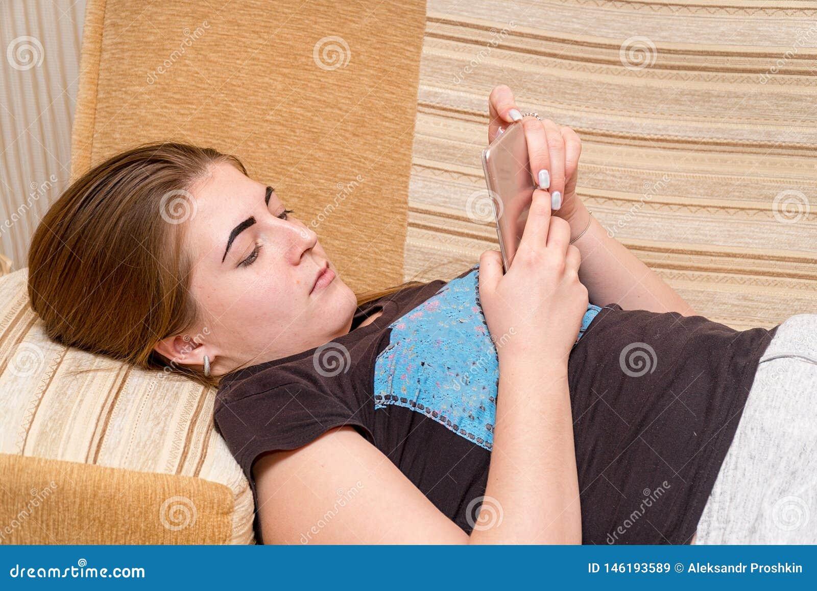 Fille se trouvant sur le divan utilisant le téléphone pour communiquer