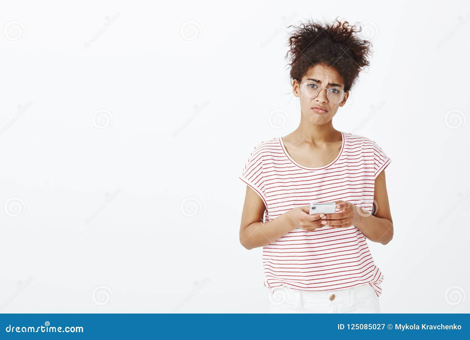 Fille sentant malheureux dumbed par l intermédiaire du téléphone Portrait de femme mignonne contrariée sombre dans les verres et
