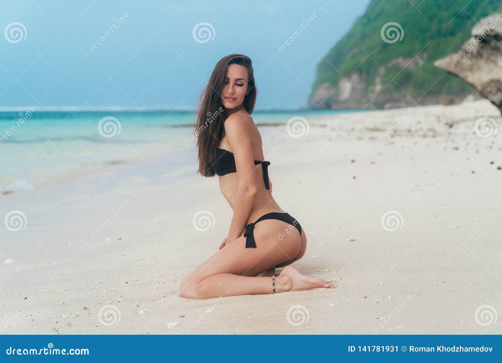 Fille sexy avec le corps sportif dans des poses noires de bikini sur la plage avec l océan bleu au fond