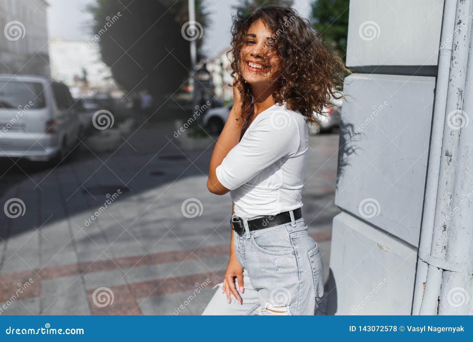 Fille sexy de belle brune marchant dans la ville avec le long vol de cheveux bouclés sur le vent