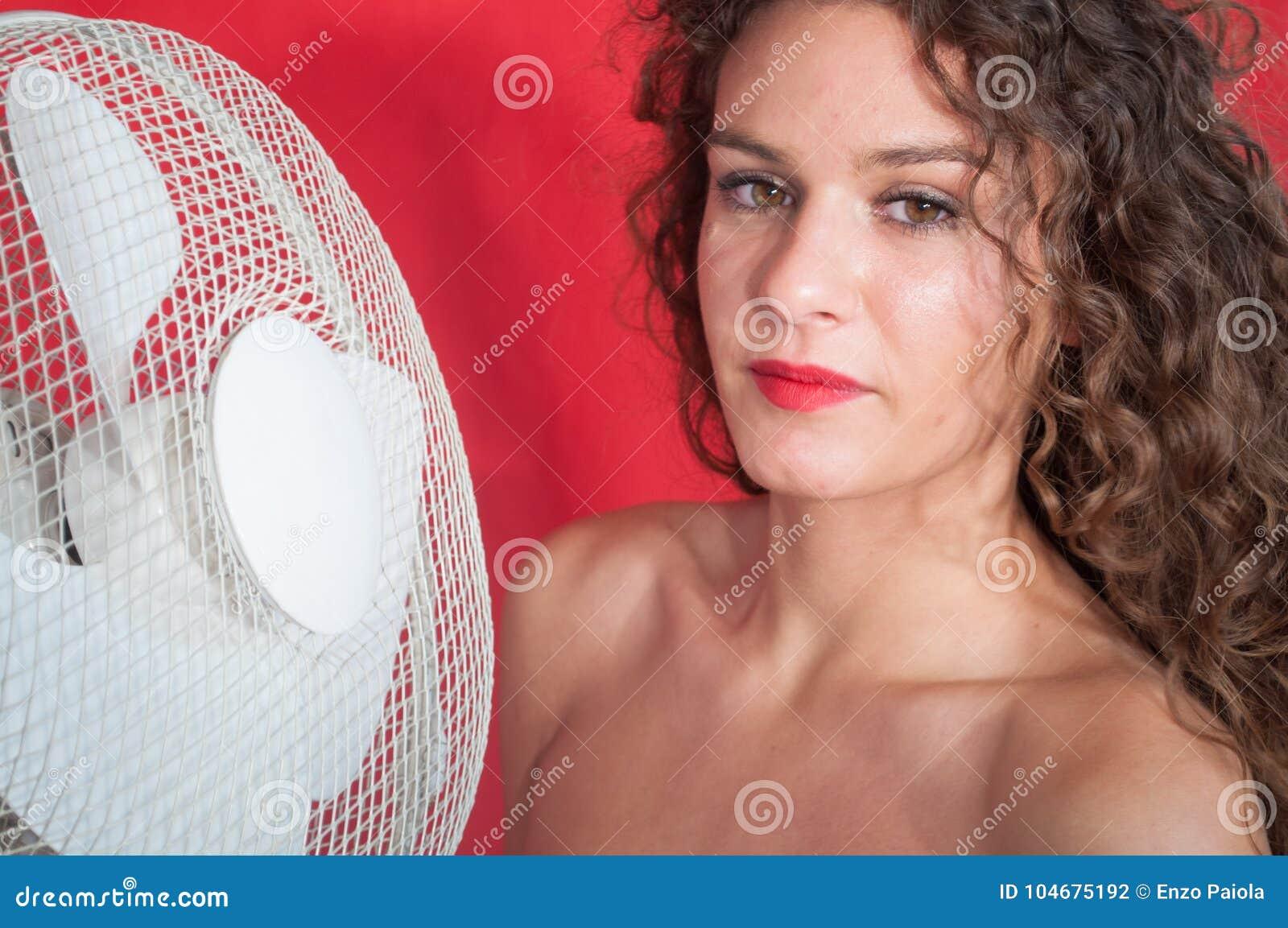 Fille sexy de brune avec les cheveux bouclés avec le ventilateur