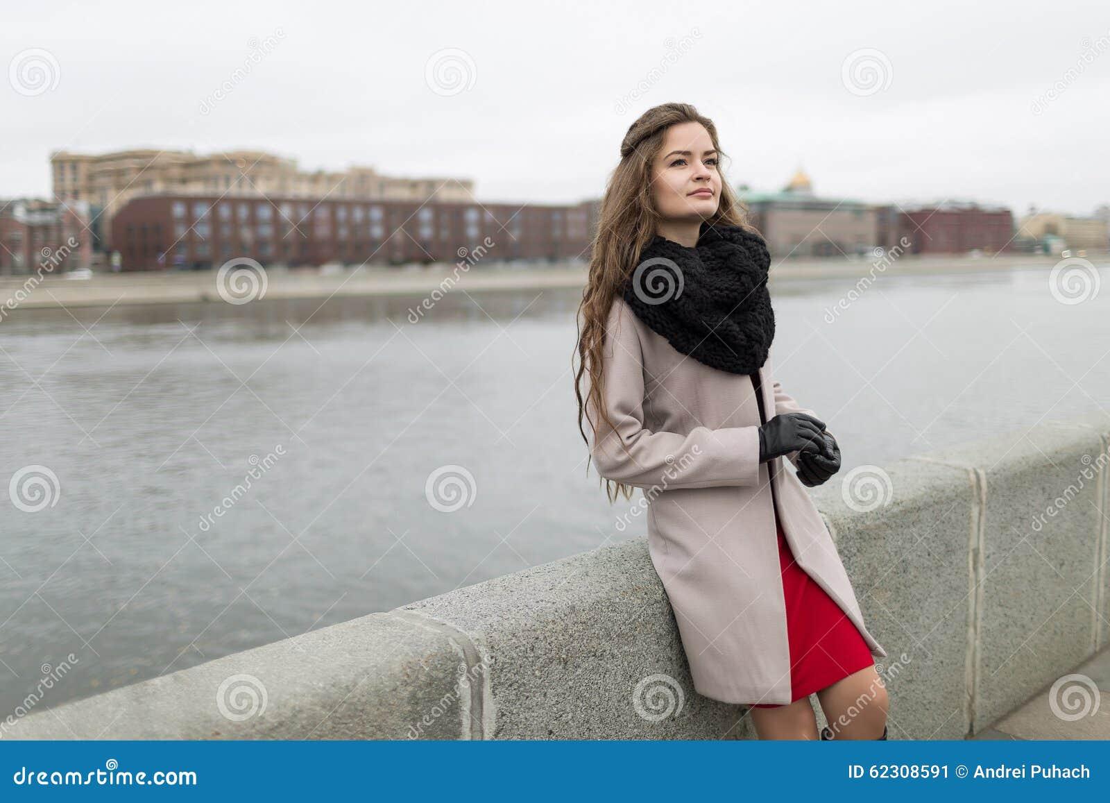 Fille sexy se tenant sur le bord de mer en automne Fille dans un manteau  noir, une écharpe et une robe rouge contre un ciel gris Non d isolement  Croisement ... 9e10d8a2d52