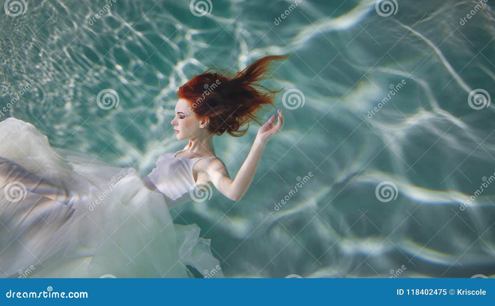 Fille sous-marine Belle femme rousse dans une robe blanche, nageant sous l eau