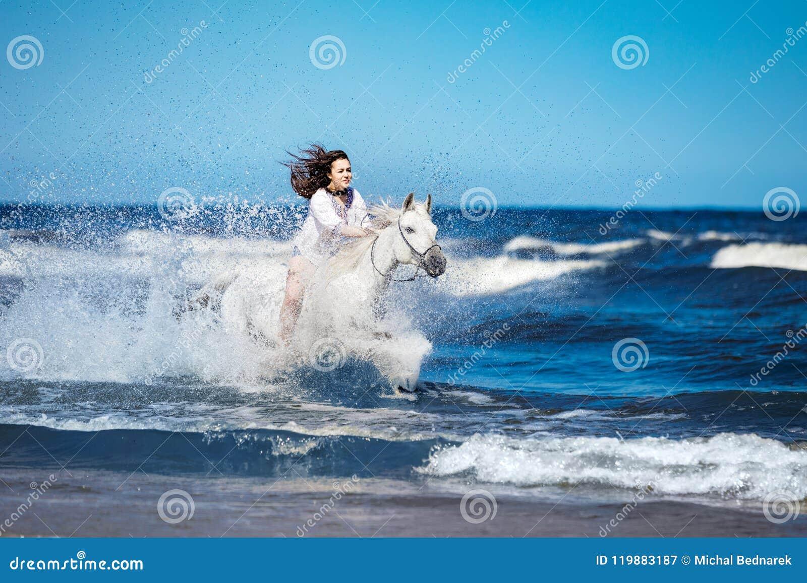 Fille sur un cheval blanc fulminant par l eau