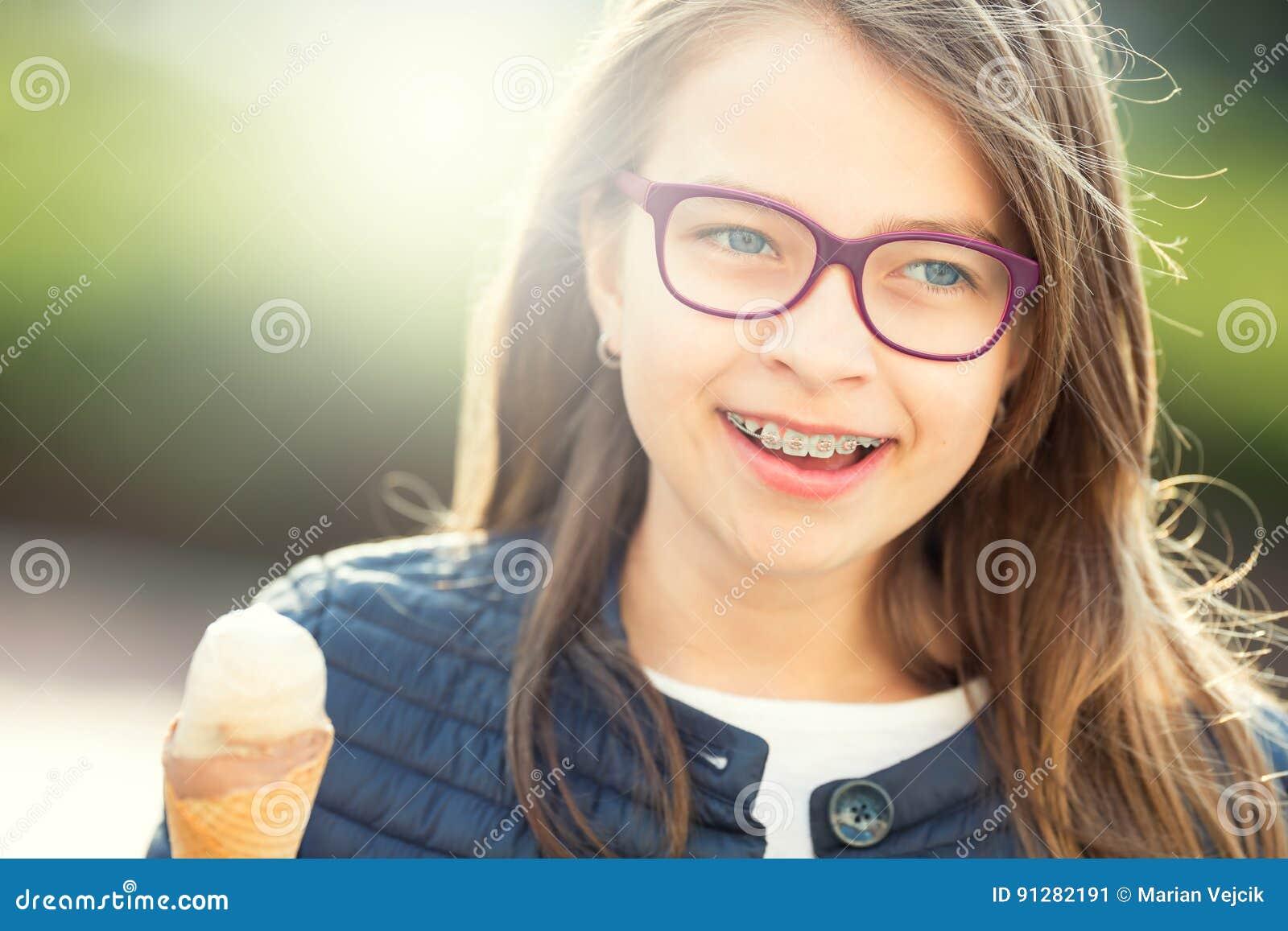 Fille teen Pré ado Fille avec la crême glacée Fille avec des verres Fille avec des accolades de dents