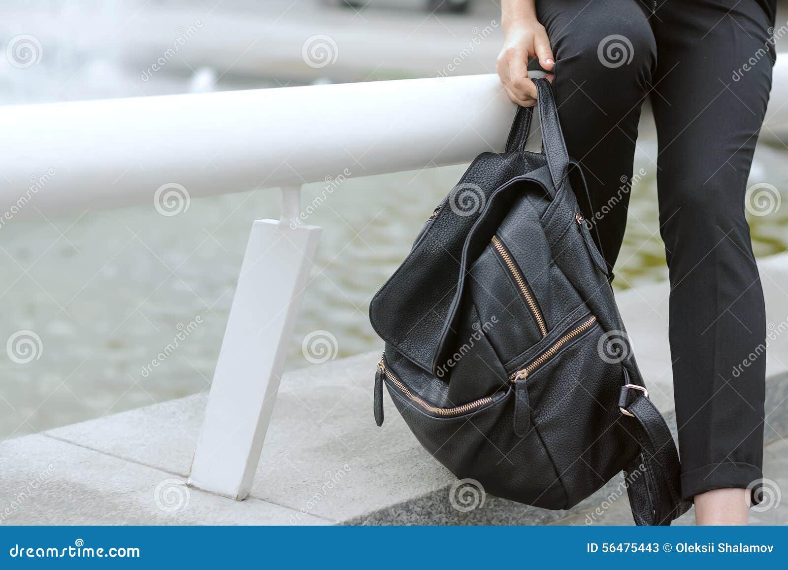 Fille tenant un sac à dos lourd dans sa main