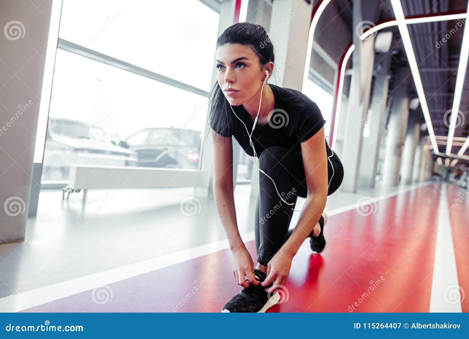 Fille vers le bas pour faire des dentelles au gymnase de forme physique avant séance d entraînement courante d exercice