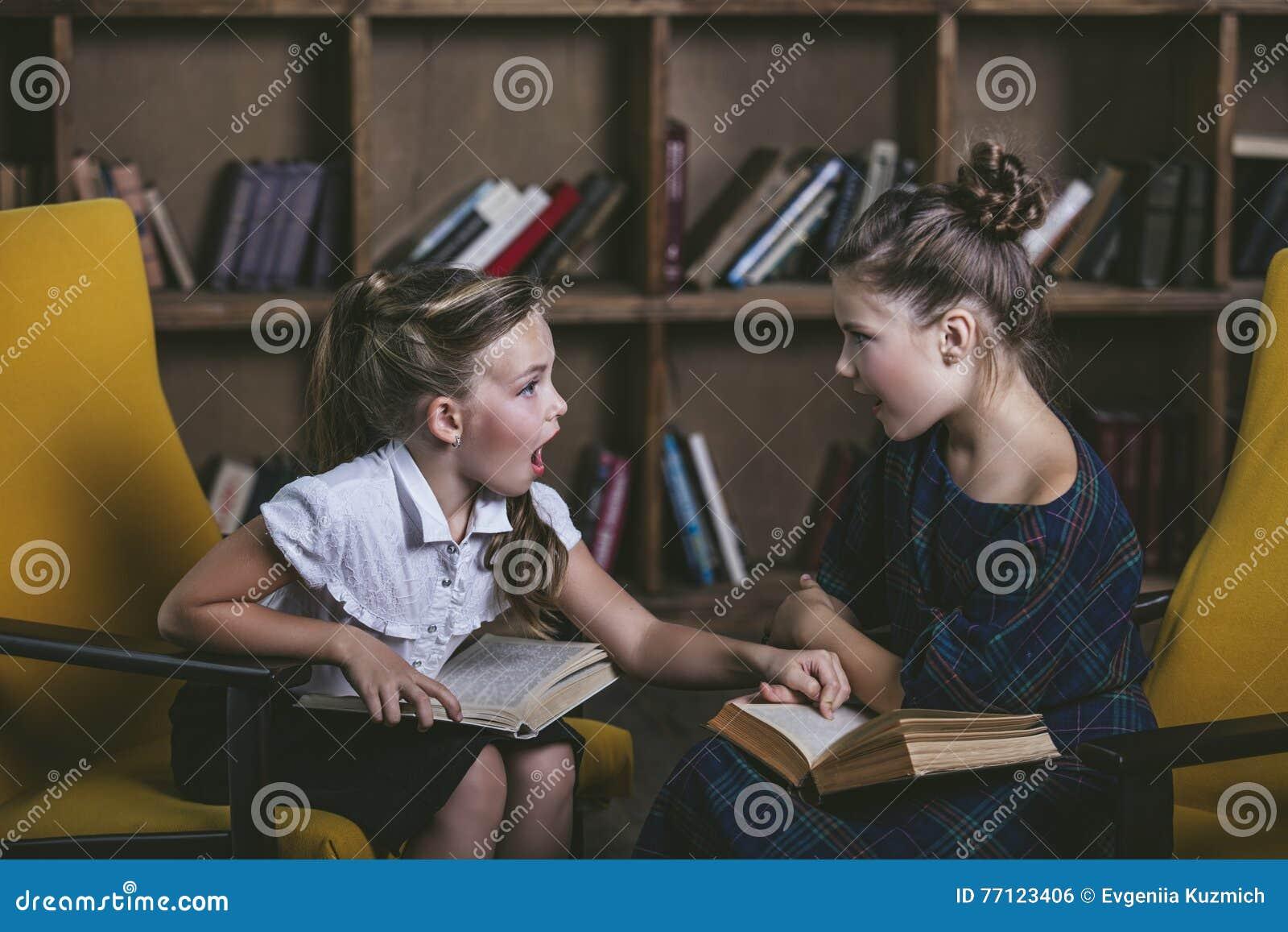 Filles d enfants dans la bibliothèque avec des livres dans l éducation