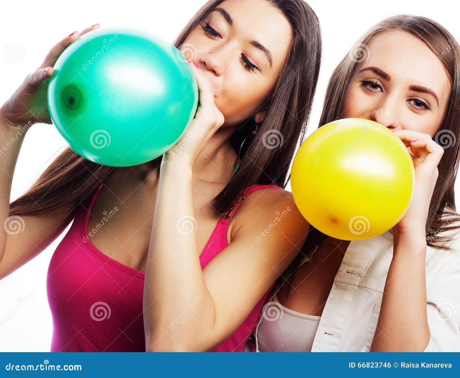 Filles de hippie souriant et tenant les ballons colorés