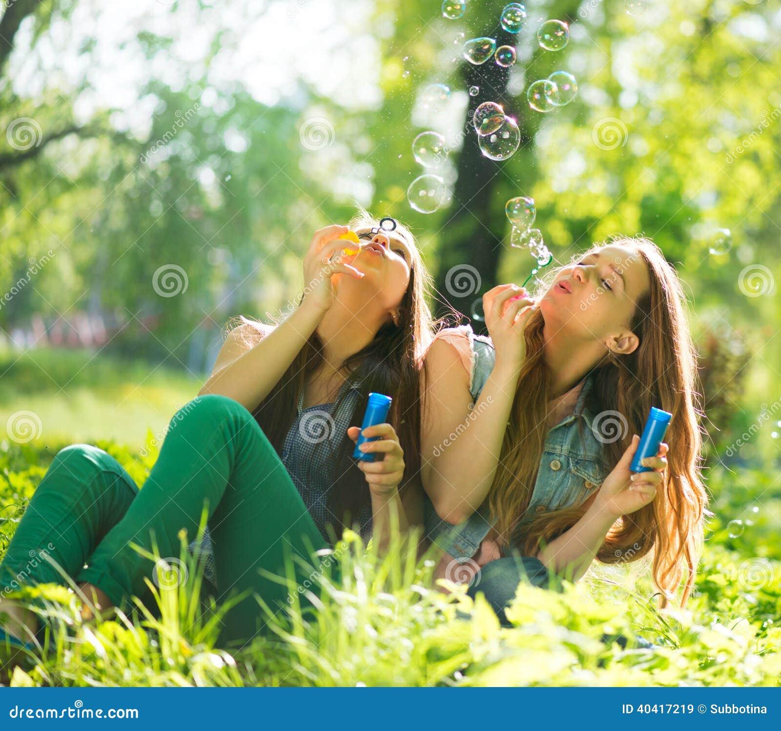 Filles de l adolescence riant et soufflant des bulles de savon