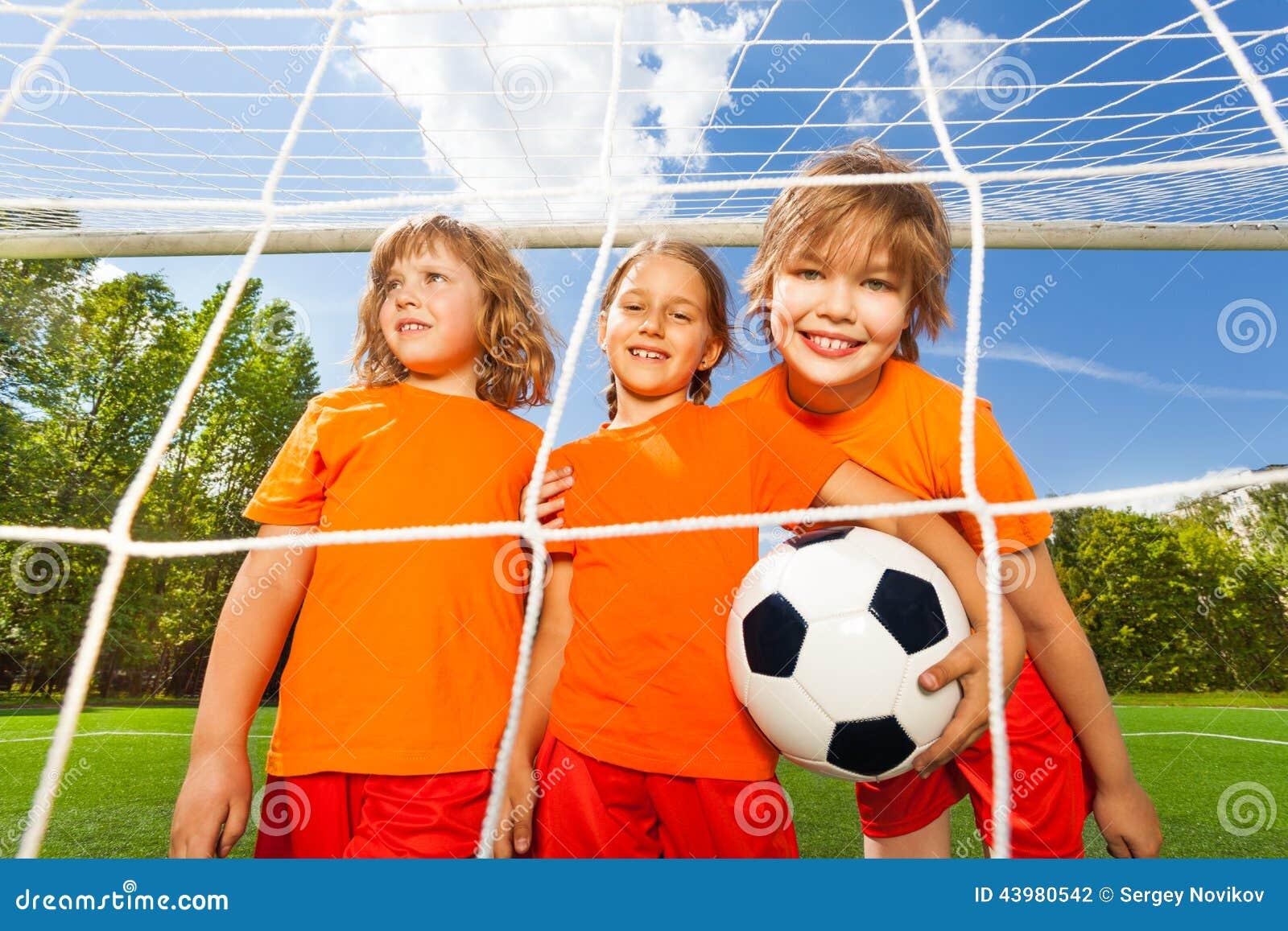 Filles de sourire avec le support du football derrière le filet